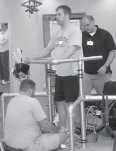 Rob Summers, center, receives intensive physical therapy in Louisville. Summers was paralyzed below the neck in a 2006 car accident and is now able to stand and move during therapy sessions with the stimulator turned on. (AP Photo/ Courtesy of Rob Summers)