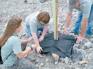Jenkins students Mercedes Boggs (left) and Bill Holbrook (center) helped plant an American chestnut tree.