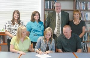 Kelsey Mullins, a senior at Letcher County Central High School, signed scholarship papers on May 23 to run cross country at the University of Pikeville. Pictured are (front row, from left) her mother Andrea Mullins, Kelsey Mullins, her father Richard Mullins, (back row) LCHS Asst. Coach Cassie Stamper, LCCHS Asst. Coach Faye Collier, University of Pikeville Head Cross Country Coach John Biery and LCCHS Head Cross Country Coach Sallie Hubbard. (Photo by Suzan Maddin)