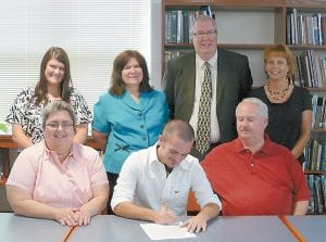 Letcher County Central High School senior Tyler Smith signed scholarship papers on May 23 to run cross country at the University of Pikeville. Pictured are (front row, from left) his mother Debbie Smith, Tyler Smith, and his father Bob Smith. Pictured in back row are same coaches identified in picture at top. (Photo by Suzan Maddin)