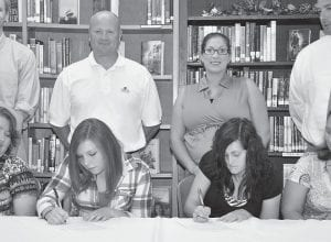 — Jenkins senior softball players Sierra Kiser (left) and Leshia Fleming (right) have signed letters of intent to play softball for the University of Pikeville. Kiser was the team's catcher this past season, while Fleming played first base. The two were joined by family members and teammates at the signing, as well as coaches, past and present. Among those coaches were University of Pikeville softball coach Robert Staggs and Jenkins Lady Cavaliers softball coach April Damron-Charles. (Photo by Chris Anderson)