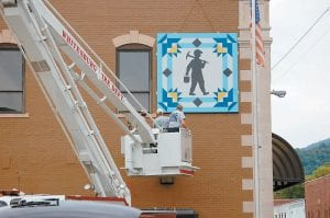 NEW QUILT SQUARE UP — Lanny Day, City of Whitesburg carpenter, artist Ked Sanders and Whitesburg firefighter Perry Fowler mounted a barn quilt square on the side of the Whitaker Bank building in downtown Whitesburg on Tuesday. Sanders and Bessie Shepherd painted the design, which was created by bank employee Margaret Hammonds, who incorporated the Whitaker logo and a coal miner into the design. (Photo by Sally Barto)