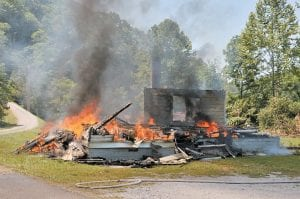In photo above, a house at Payne Gap burned as part of a training excercise for the Neon and Jenkins Volunteer Fire Departments recently. A Neon fire department spokesperson said the owners of the home filed paperwork to have the structure torched and the two departments took the opportunity to use the controlled burn as a training excercise. In photo at right, Neon Volunteer Fire Chief Carter Bevins (seated) spoke with members of his department as they cooled off after fighting the flames. (Photos by Chris Anderson)