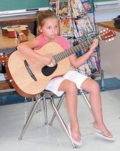 TUNED IN — Madison Baker, 7, listened to an instructor at the Cowan Creek Mountain Music School at Cowan Elementary School. She was one of 161 students who learned how to play traditional mountain music last week.