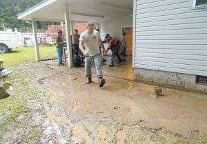 CHIPPING IN — Friends, neighbors and relatives helped clean floodwaters from the home of Johnny and Janet Napier of Little Cowan late Monday afternoon after flash flooding hit the community. (Photo by Caressa Maggard)