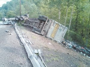 Charles Smith, 46, of London, died after the tractor and garbage-filled trailer he was driving overturned Monday while Smith was driving north on KY 15 near the Knott-Letcher county line. (Photo by Connie Fields)