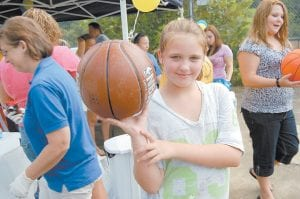 Kahlan Adams posed for a photograph with a new basketball she received from the Rotary Club of Whitesburg during a dedication of new goals and basketballs Rotary members purchased for the court at the Whitesburg Housing Authority in West Whitesburg. More coverage inside.