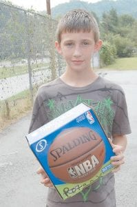 Chase Adams posed for a photograph with a new basketball he received.