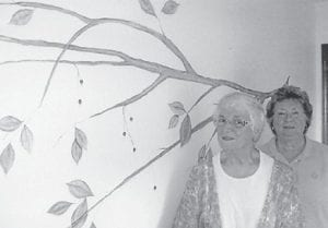 Verna Rayburn recently painted a mural for her friend, Nelda Harlowe. It took Rayburn about 20 hours to complete the acrylic painting of a tree on a wall in Harlowe's laundry room. Pictured are Rayburn and Harlowe.