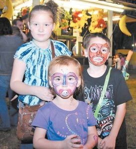 Kenzie Cross (left), Morgan Williams and Hunter Coots showed off their freshly painted faces at Isom Days.