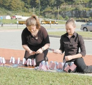 Sisters Kristen and Halie Moushon, both students at Letcher County Central High School, placed American flags in front of the high school Sunday to commemorate the 10th anniversary of the terrorist attacks on New York City, Washington, D.C., and in Pennsylvania on September 11, 2001. (Photo by Sally Barto)