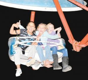 — Daysha Carter, Carlee Kincer and Isabell Thomas mugged for the camera while riding the Paratrooper at the Mountain Heritage carnival Friday night. (Photo by Chris Anderson)