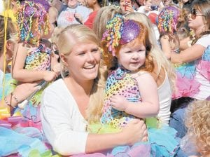 MOTHER AND DAUGHTER — Paige Adams carried daughter Karsyn as part of a group of young twirlers.