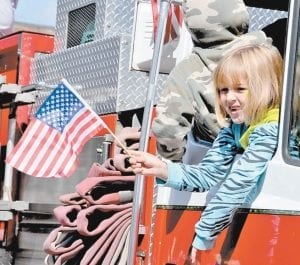 SHOWING THE COLORS — Kennedy Harvey greeted the crowd with a wave of the United States flag as she leaned out the window of a Kingscreek Fire Department truck during the 2011 Mountain Heritage Festival Parade on Sept. 24.