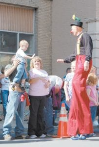 Three-year-old Dalton Hensley, of Pound, Va., gave a very tall clown a high five during the Mountain Heritage Festival Parade in Whitesburg on Saturday. (Photo by Sally Barto)