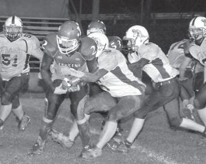 WRAPPED UP IN HIS WORK — Jenkins quarterback Kevin Brown is overtaken by the Knott Central defensive line during the Cavaliers' win over the Patriots on Friday night.
