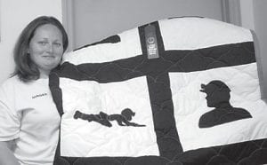 Ginger Isaac of McRoberts, is pictured with a Coal Miner Quilt made for her brother, Russell Fleming. The quilt won first place in the Mountain Heritage quilt contest held by the Letcher County Extension Office. She says she really enjoys making quilts for family and friends.