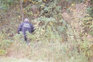 A Kentucky State Police officer kept check on a black bear after the bear, pictured below, found its way to a ditch after being hit by a car Tuesday. The bear was later euthanized.