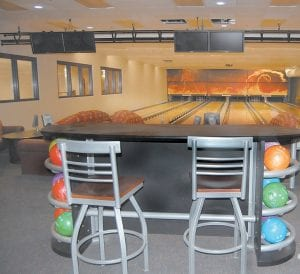 The six-lane bowling alley (above) has a large projection screen with a sound system and DVD player. During cosmic bowling the lanes light up with 60 black lights. The bowling alley is also stocked with shoes to fit young children and adults. Pictured below is a kid's size nine shoe and a men's size 12 shoe.