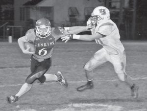 Jenkins High School's Cody Childers stiff-armed a defender on a rushing attempt in last Friday night's loss to Harlan, 52-28. The Cavaliers broke out to a 22-0 first quarter lead, but fell flat. The Green Dragons took the lead before halftime while the Cavs were only able to muster a single scoring drive for the rest of the game. Jenkins fell to 1-8 on the season with the loss and will finish up the regular season at home against Betsy Layne on Friday. (Photo by Chris Anderson)