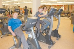 Twelve-year-old twins Jonathan and Nicholas Sergent tried out new exercise bikes with their mother Liz Sergent of Whitesburg during the open house of the Letcher County Recreation Center in Whitesburg. A ribbon cutting ceremony was held at the center Oct. 22, but the facility isn't quite ready to open yet. (Eagle photo)