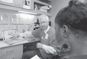 In this photo provided by College of American Pathologists, a pathologist explains a Pap test slide to a patient in Minneapolis, Minn.