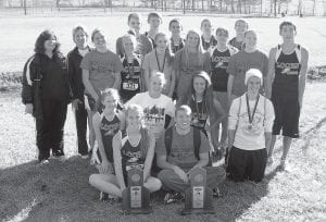REGION'S TOP TEAMS — The Letcher County Central High School girls' and boys' cross country teams brought home championship trophies from the Class 2A Region 7 Cross County Championship held Nov. 5 in Winchester. The runners were welcomed home with congratulations written on the Food City billboard as well as a chilly drive through town on a Whitesburg fire truck. Several supporters of the team followed with horns blowing loudly. The state meet will be held Nov. 12 at the Lexington Horse Park. Pictured above are (back row, from left) Brad Collier, Anthony Banks, Austin Bolling, Nick Boggs, Chippy Frazier, (third row, from left) Coach Faye Collier, Coach Sally Hubbard, Amber Crawford, Keisha Balthis, Freddi Adams, Angelina Gose, Sam Mullins, Mariah Mullins, Dillon Burton, (second row, from left) Leanna Bryant, Endia Lillie, Carlenia Gose, Chase Cates, (front row, from left) Nicole Banks and Trenton Whitaker with first-place trophies.