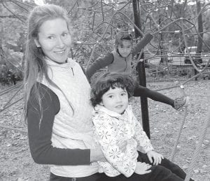 Michele Pereira posed at a park in Ashland, Ore., while holding her daughter Genevieve, 2, as her daughter Evangeline, 6, played in the background. A registered nurse, Pereira is among the growing number of parents questioning mandatory vaccinations for children. (AP Photo)