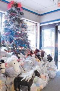 """Presents were piled high under and around a large Christmas tree (above) as volunteers (below) worked to get ready for Marlow Tackett's """"Christmas for the Needy,"""" which will open Sunday morning at 10. (Photos by Marcie Crim)"""
