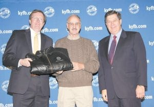 In this photo, Howard Stanfill, center, accepted an award for outstanding membership and program achievement from David S. Beck, right, Kentucky Farm Bureau executive vice president, and Bradley R. Smith, left, executive vice president of Kentucky Farm Bureau Insurance Companies, during the December 2 recognition and awards program.