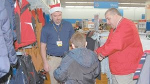 Jason Higgins, manager of the Whitesburg Walmart, watched as Kentucky State Police Det. Gary Sandlin picked out a new coat for a child at the 'Shop With a Trooper' event.