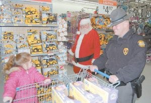 """At right, a little girl asked Santa Claus where his reindeer were during the Kentucky State Police """"Shop With A Trooper"""" event held at the Whitesburg Walmart Dec. 9. Also pictured is KSP Trooper Adam Hall. Santa was played by Red Roberts of Hemphill. Eighty-two children from Letcher, Knott, Leslie, Perry and Breathitt counties shopped with a trooper and were each able to spend $125 on clothes, toys and other items."""