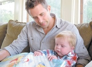 Matt Hammitt, lead singer for the Christian rock band Sanctus Real, reads a book to his 1-year-old son, Bowen, at their home in Perrysburg, Ohio. Hammitt has released an album inspired by Bowen, who was born with a rare heart defect. (AP Photo)