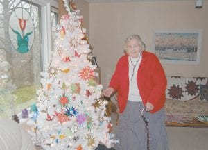 Lorraine Waddles, 80, of Whitesburg, posed for a photograph Tuesday morning in front of her Christmas tree, which she decorated with origami decorations.