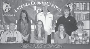 Four Letcher County Central High School seniors have signed letters of intent with the University of Pikeville to run cross-country and track. The scholarship recipients are (from left) James Trenton Whitaker, Christie Nicole Banks, Freddie Renee Adams and Bradley Collier. Pictured at back are Lindsey Gibson, a recruiter for University of Pikeville; John Biery, coach of the University of Pikeville cross country and track team; and Denise Yonts, Letcher County Central assistant principal.