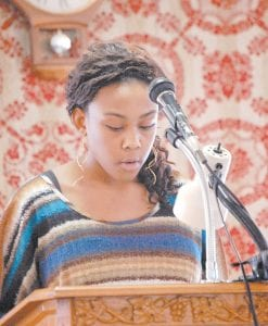 Nia Meadows, 14, of McRoberts, read biographical information about Dr. Martin Luther King Jr. on Monday during a program at Church of God Militant Pillar and Ground of the Truth in McRoberts. Meadows is an eighth-grade student at Jenkins Middle School. Related story inside. (Photo by Sally Barto)