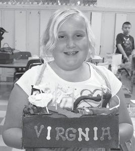 a student at Fleming-Neon Elementary School, is pictured holding a parade float she made which is decorated with identifying characteristics of Virginia. Fifty floats were made by Fleming-Neon students, who participated in the parade of states.
