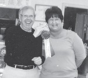 """Debbie Slone was presented with a blue ribbon by Jim Craft in honor of her chicken and dumplings. The ribbon says """"Dumplin' Maker Number One'."""