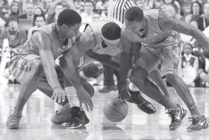 CATS HANDLE VOLS — Kentucky's Terrence Jones, left, and Marquis Teague, right, and Tennessee's Jarnell Stokes battled after a loose ball during the first half of Tuesday's game in Lexington. (AP Photo/James Crisp)