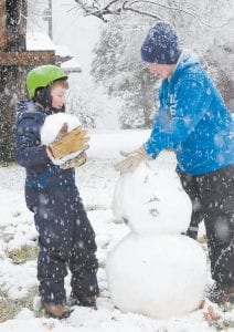 Brothers Judson and Sam Collins of Whitesburg built a snowman while snow continued to fall around 4 p.m. on Feb. 19. Judson is 13. Sam is 8. (Photo by Sally Barto)