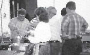 Buddy Roe is shown instructing his fellow teachers on the art of making gravy for the faculty breakfast.