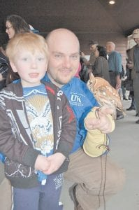 Five-year-old Joshua Adams posed for a photograph with Letcher County Agent Jason Brashear and the screech owl Joshua recently found that was injured. The owl is being cared for through the Letcher County Extension Office's raptor rehabilitation program and will eventually be released back into the wild.