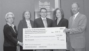Lonnie Lawson (far right), president and chief executive officer of The Center for Rural Development, presents Dr. David Narramore (center), chairman of the Letcher County Tourism and Convention Commission, with a $10,000 Appalachian Regional Commission (ARC) mini-grant to advance strategic planning efforts in the region. Also pictured are Sue Moreland (left) of the ARC Washington, D.C. office; Peggy Satterly (second from left), manager of the Kentucky ARC Program; and Lynn Littrell (fourth from left), executive director of the Office of the Governor, Department for Local Government. The tourism commission received the grant through The Center's Developing and Implementing Community Strategies Program at the ARC Summit held March 30 in Somerset.