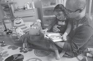 Christopher Astacio reads with his daughter Cristina, 2, recently diagnosed with a mild form of autism, in her bedroom on in New York. Autism cases are on the rise again, largely due to wider screening and better diagnosis, federal health officials said. (AP Photo)