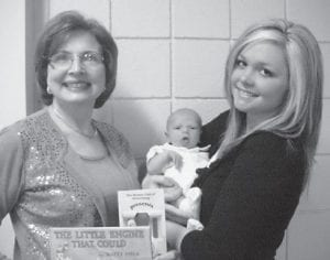 """Drew Whitaker, son of Brooke and Christopher Whitaker, was the 100th child to register for Dolly Parton's Imagination Library, sponsored by the Rotary Club of Whitesburg. He was presented a book, """"The Little Engine That Could"""", by Rotary President Margaret Hammonds. Pictured are (left) Hammonds and Brooke Whitaker holding Drew. Children under five years old who live in the Whitesburg Zip Code area may register to receive the free books every month until they are five years old. For more information, call Hammonds at 633-8200."""