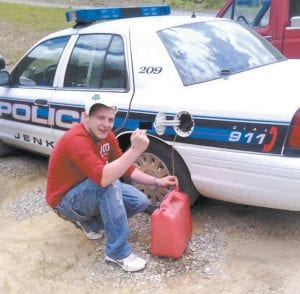This photo showing Michael A. Baker of Mayking syphoning gas from a Jenkins Police cruiser resulted in Baker's arrest after it appeared on Facebook.
