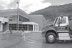 Whitesburg firefighters Robert Keith and Perry Fowler washed pavement in front of the newly built Letcher County Area Technology Center Tuesday afternoon. The men were getting the parking lot ready for a ribboncutting ceremony featuring Gov. Steve Beshear as the keynote speaker.