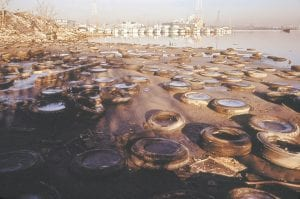 """YESTERDAY — In this January 1973 photo released by the U.S. National Archives, trash and old tires littered the shore at the Middle Branch of the Patapsco River in the harbor of Baltimore, Md. This archival image was part of the """"Documerica"""" project, begun in 1972 by the then-new Environmental Protection Agency. (AP Photo/U.S. National Archives, Jim Pickerell)"""