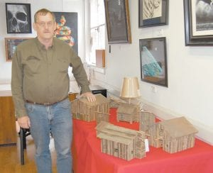 Jerry Howard of Knott County stands next to miniature replicas he made of barns, cabins and outhouses using wood from structures that are at least 100 years old. His work will be on display at the 229 Underground Gallery in downtown Whitesburg during the Redbud Artwalk this weekend.
