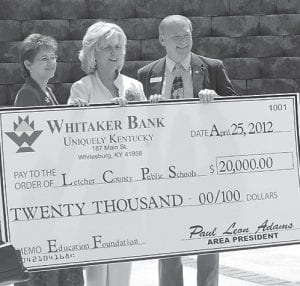 Marie Amburgey, an employee with Whitaker Bank, posed for a photo with Letcher Schools Supt. Anna Craft and Paul Leon Adams, president of Whitaker Bank, in Whitesburg at the ribbon-cutting ceremony for the Letcher County Area Technology Center. The board was presented during the ceremony with $20,000 checks from Whitaker Bank and Community Trust Bank, as well as a $25,000 check from Alpha Natural Resources.
